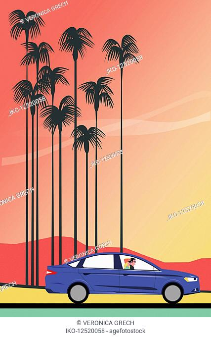 Happy couple driving past tall palm trees at sunset