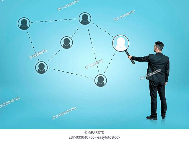 Back view of a businessman enlarging one of the social network icons connected by dotted lines with a magnifier. Searching and investigation
