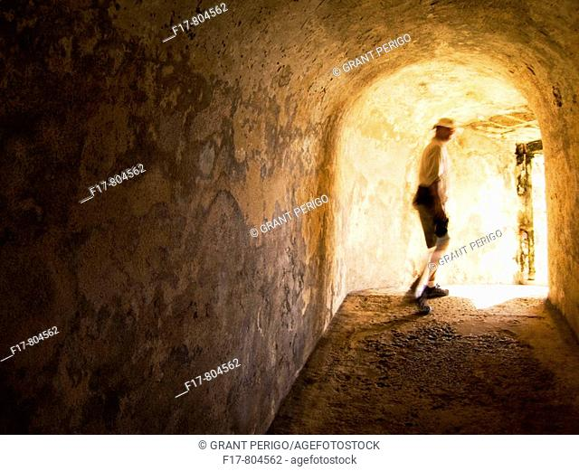 a man walking into the light at the end of a tunnel