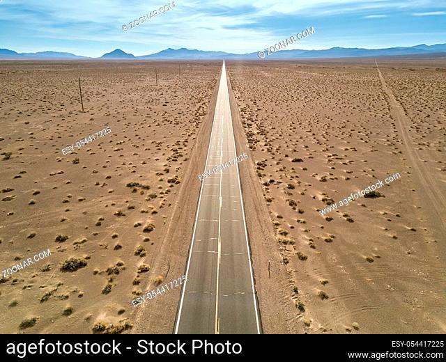 Drought landscape of Death Valley with a highway on the background of the mountains and cloudy sky in the USA. Aerial horizontal photo
