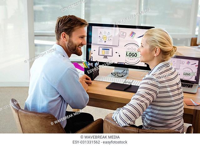 Smiling executives interacting at desk