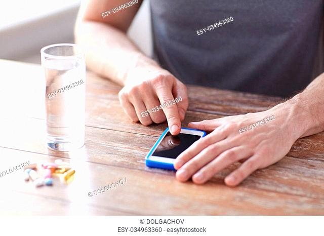 medicine, technology, nutritional supplements and people concept - close up of male hands pointing finger to blank smartphone screen, pills and water on table