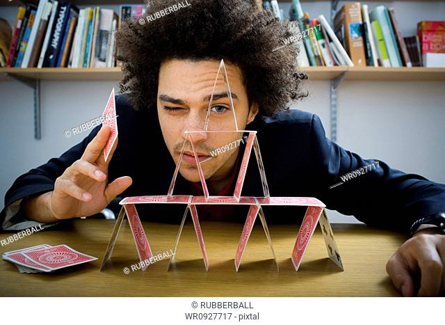 Man making a pyramid out of playing cards