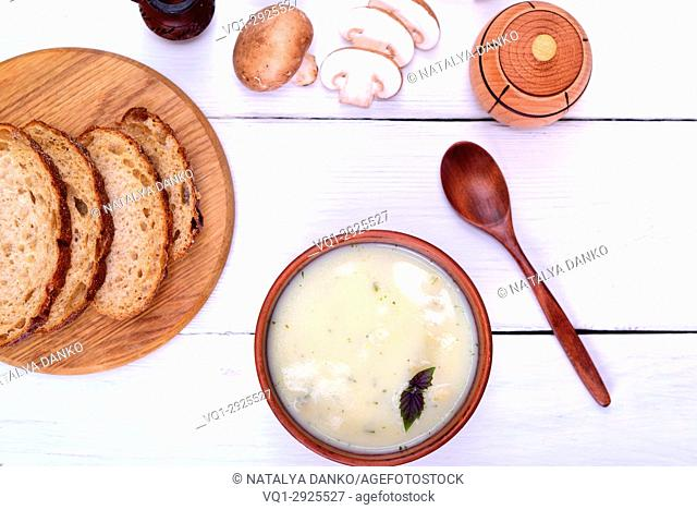 Cream mushroom soup with champignons on a white wooden table, top view