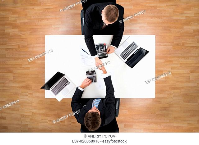 Directly above shot of businessmen shaking hands while calculating finance in office
