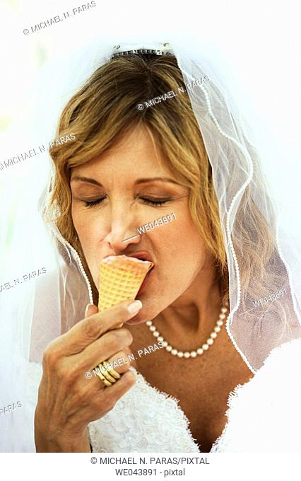 Bride eating ice cream cone with eyes closed