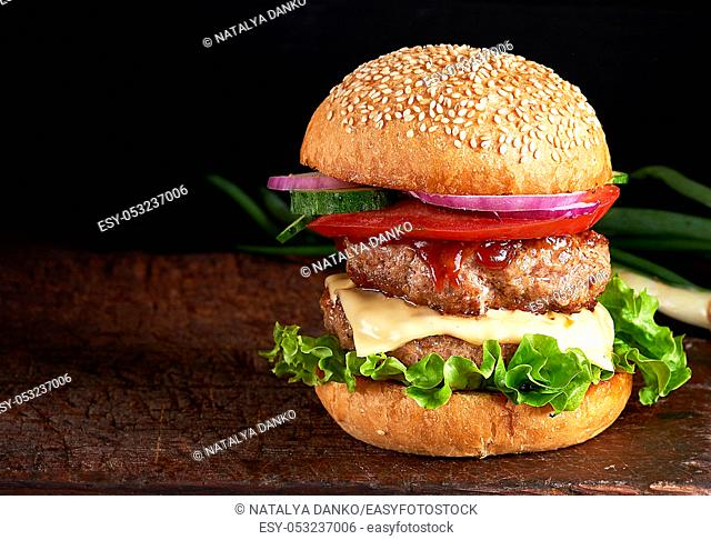 large burger with two fried cutlets, cheese and vegetables in a round wheat flour bun, copy space