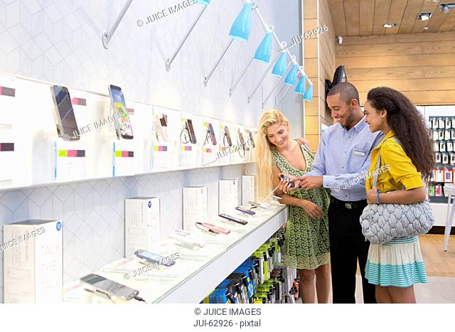 Store manager assisting two female customers in phone store