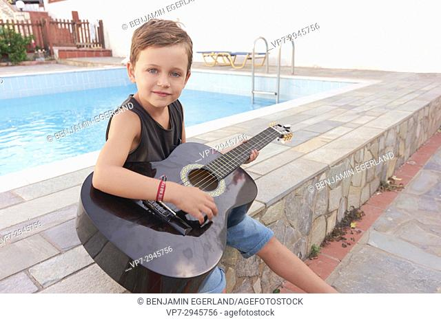 boy with guitar next to pool. Australian ethnicity. During holiday stay in Hersonissos, Crete, Greece