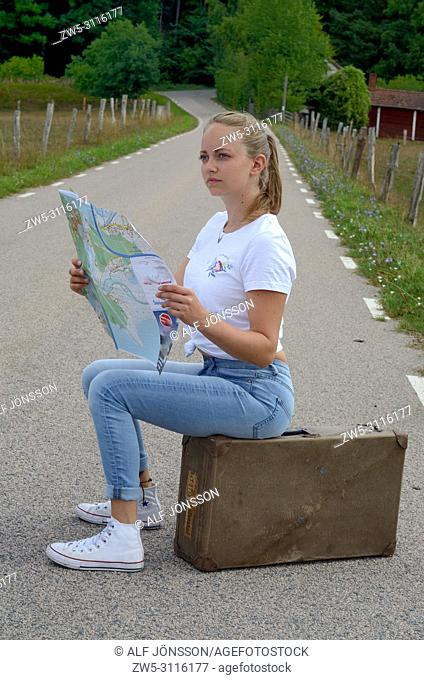 Young woman 25 years old, read a map sit on an old suitcase on a country road in Scania, Sweden, Europe