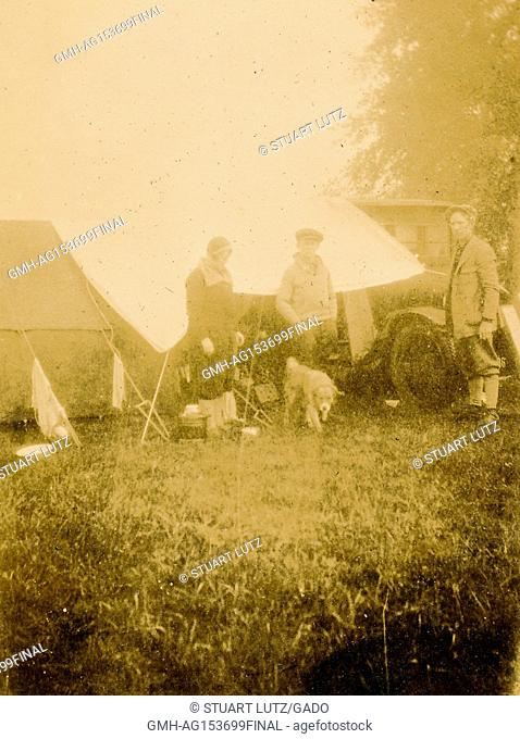 A family with their dog stands beside their automobile at a camp site during a road trip through New England, 1925. ()