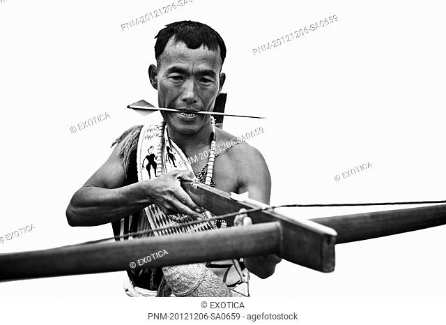 Naga tribal warrior holding a cross bow, Hornbill Festival, Kohima, Nagaland, India