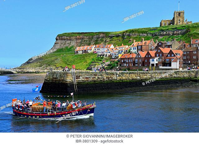 Excursion boat entering the harbour, St. Mary's Church at back, Whitby, North Yorkshire, England, United Kingdom