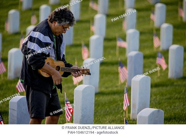 Man playing on an ukulele in the midst of rows of tombstones decorated with Star-Spangled Banners, at Fort Rosecrans National Cemetery on Memorial Day weekend