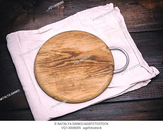 round wooden cutting board on a gray napkin, vintage toning