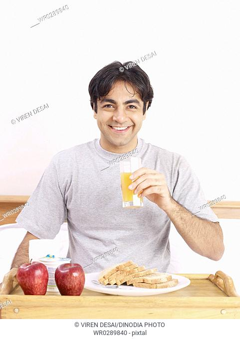 Young man holding juice glass having breakfast on bed MR702V