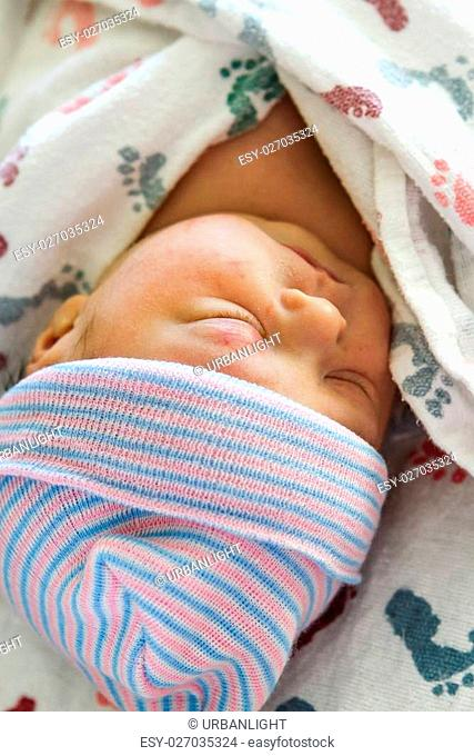 A newborn baby girl wrapped in a swaddle blanket