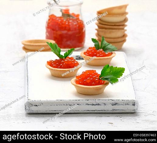 red chinook caviar in a glass jar and round tartlets on a white table, close up