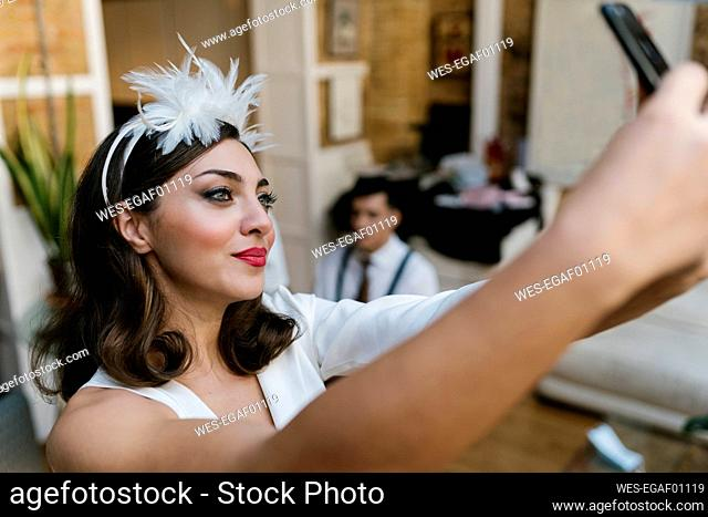 Bride taking selfie through smart phone at home