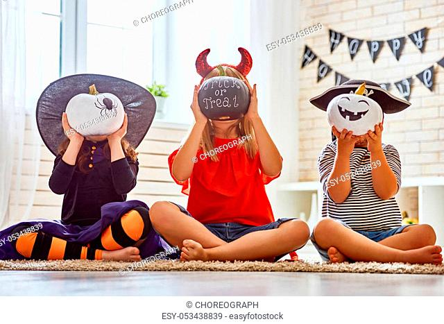 Happy brother and two sisters on Halloween. Funny kids in carnival costumes indoors. Cheerful children play with pumpkins and candy
