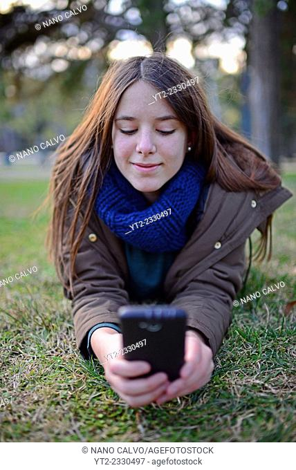 Cute teenager using mobile phone in the park