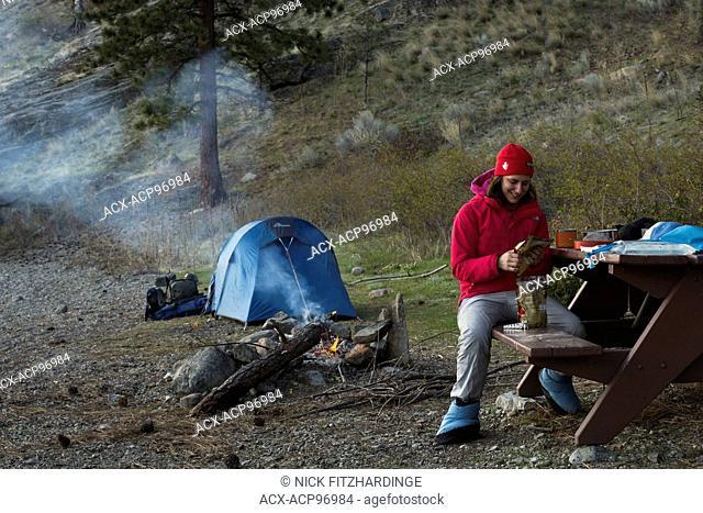 A female camper preparing a backcountry meal at Buchan Bay campsite, Okanagan Mountain Provincial Park, British Columbia, Canada