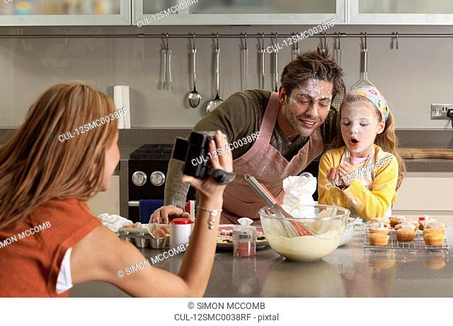mother taking picture of cooking family