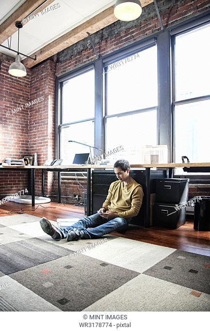 Hispanic man on his cell phone while sitting on floor at his office workstation