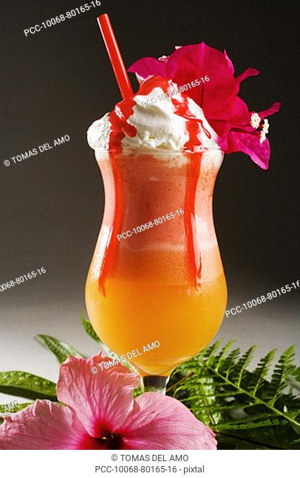 Orange and pink tropical drink topped with whip cream, dripping with strawberry syrup