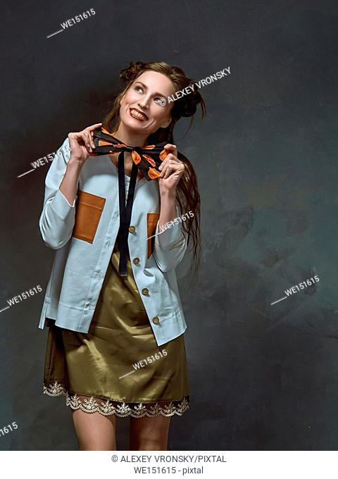 Photographing fashion collections of clothes in the Studio. Photos were taken opposite the dark gray walls. Young brunette is wearing a dress of dark green of...