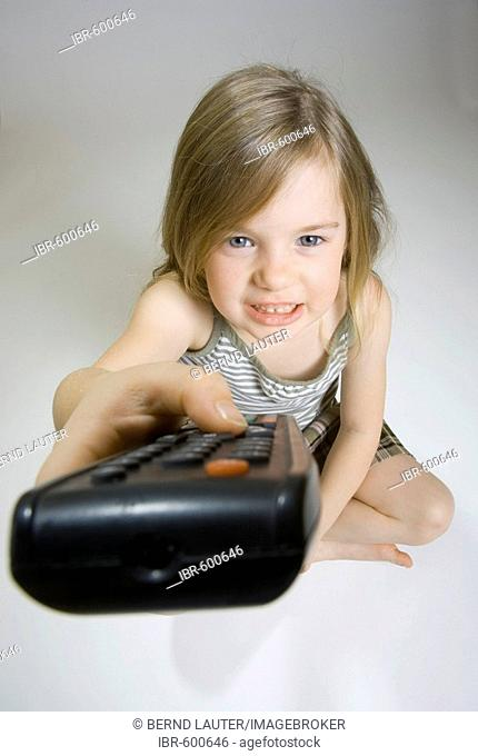 5-year-old girl holding up a tv remote control