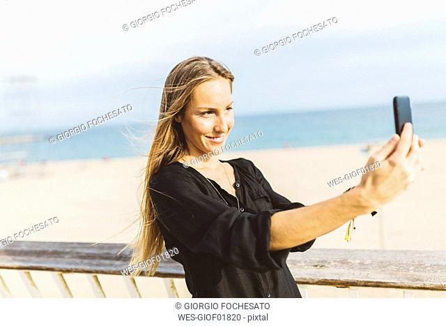 Smiling young woman taking a selfie at the beach