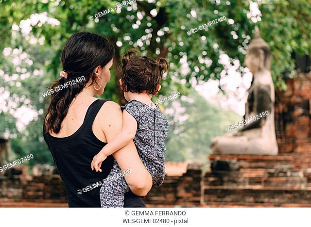 Thailand, Ayutthaya, Mother and daughter looking at a Buddha statue at Wat Mahathat
