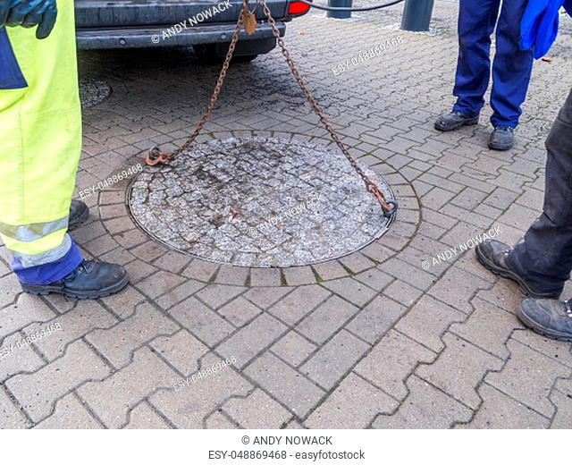 Three unrecognizable workers of the public utilities at the opening of a heavy double manhole cover by crane and steel chain and hook in a pedestrian precinct...