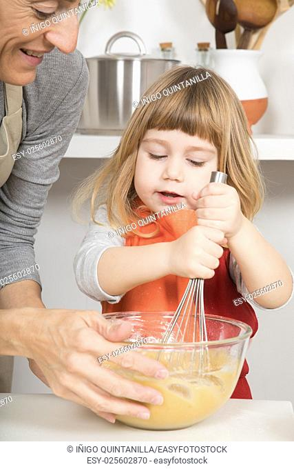 three years old child whipping cream in glass bowl with metal whisk, and woman mother in teamwork to make and cook a sponge cake at kitchen home