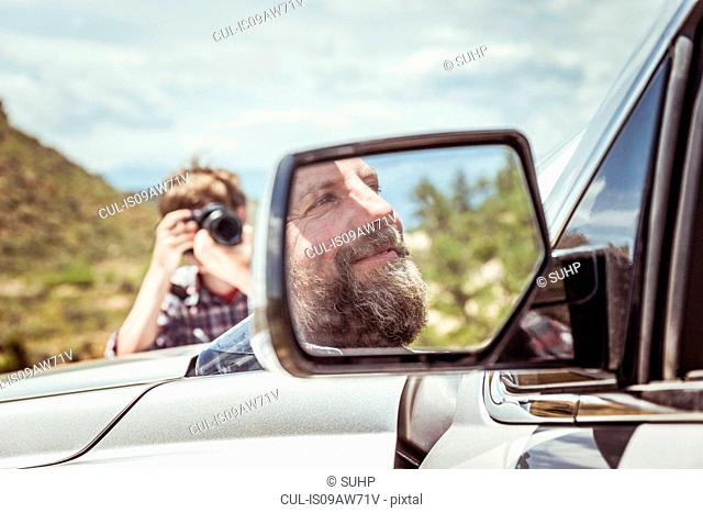 Teenage boy photographing father in off road vehicle, Bridger, Montana, USA