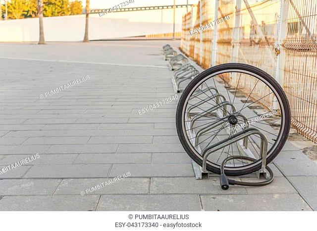 Stolen bicycle, Chained front bicycle wheel locked. A damaged bike wheel is all that is left, a single bicycle wheel on the street due to stealing