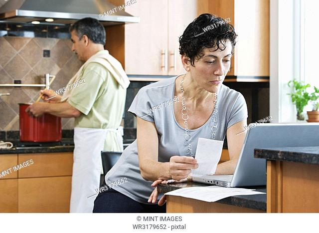 A man cooking supper at the hob, and a woman using a laptop and checking paperwork in the kitchen