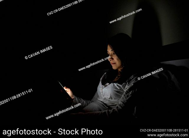 Latino woman using her cell phone before bed