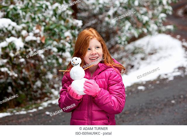Red haired girl in front of snow covered trees, wearing pink gloves and padded jacket holding snowman looking away smiling