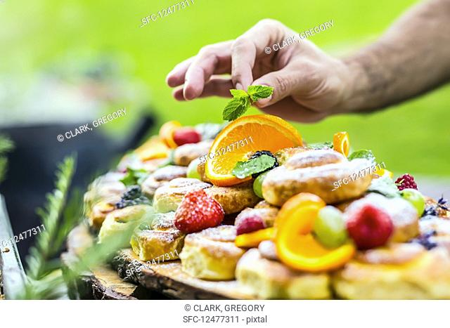 Chef prepares a plate of cakes with fresh fruits with herb decoration