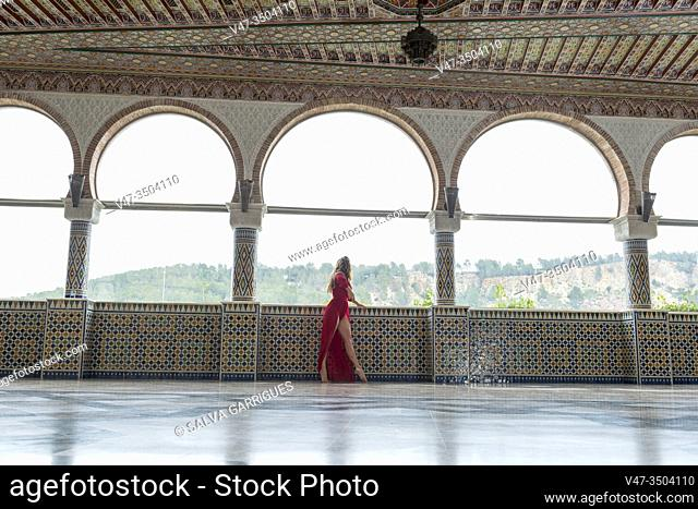 Woman in a red dress looking out a window in the halls of the Arab palace