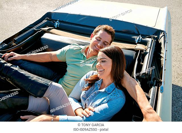 Couple relaxing in convertible car, Los Angeles, California, USA