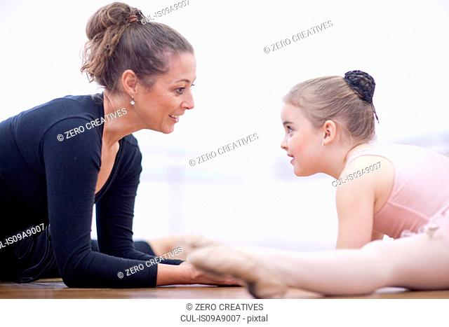 Teacher and young ballerina practicing floor stretch