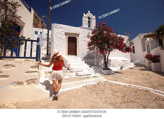 Woman in front of a whitewashed church in the old town Chora, Amorgos, Cyclades Islands, Greek Islands, Greece, Europe