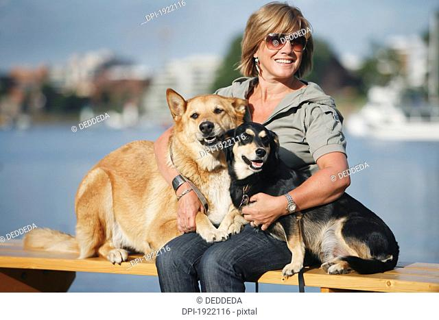 a woman embracing her two dogs by waterfront, victoria, vancouver island, british columbia, canada