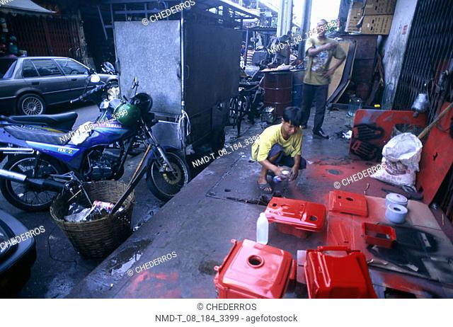 High angle view of a teenage boy spray painting, Thailand