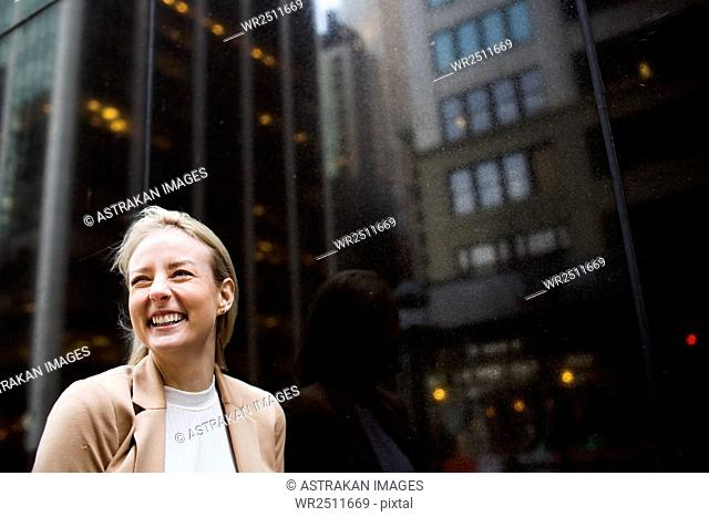Close-up of smiling businesswoman standing by glass window with reflection
