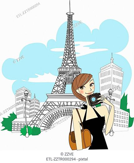 Portrait of woman standing by Eiffel tower, holding camera