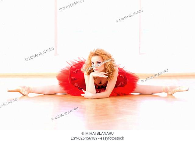 Beautiful ballerina, in split position, looking at camera with an allusive smile